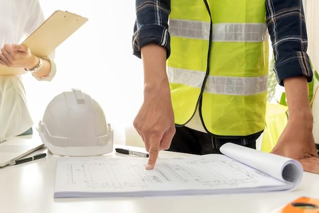 Grupo de arquiteto e engenheiro trabalhador da construção civil, planejando e analisando a planta no escritório da sala de reuniões no canteiro de obras, industrial, contrato de construção e conceito de empreiteiro