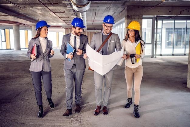 Grupo de arquitetos dedicados e altamente motivados caminhando no processo de construção e falando sobre ideias de como transformar um prédio antigo em um centro de negócios moderno.
