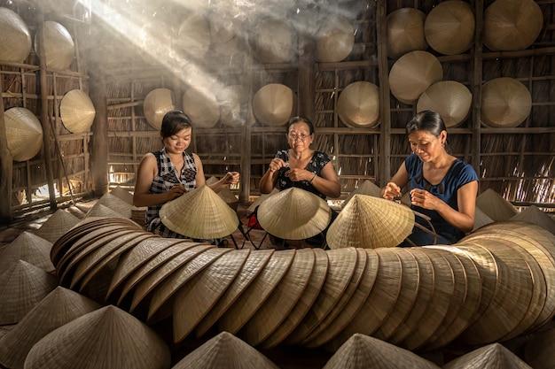 Grupo de artesãs vietnamitas fazendo o tradicional chapéu vietnamita
