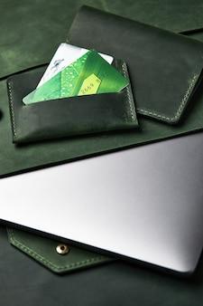 Grupo de artigos de couro verde feitos à mão em uma mesa de madeira. vista superior, close-up.