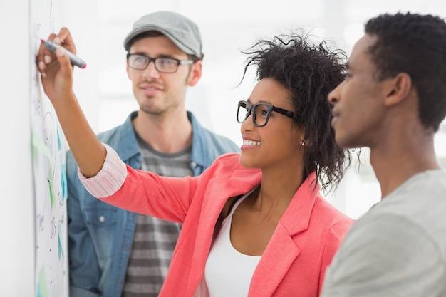 Grupo de artistas em discussão na frente do quadro branco no escritório
