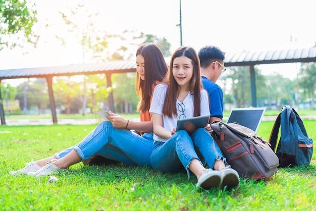 Grupo, de, asiático, estudante faculdade, usando, tabuleta, e, laptop, ligado, campo grama, em, ao ar livre
