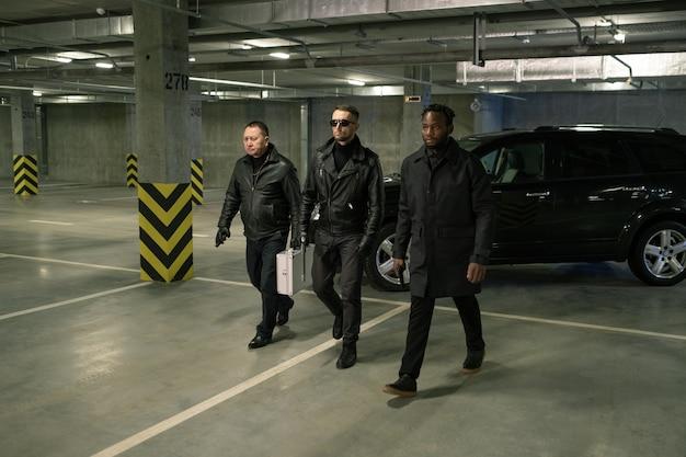 Grupo de assassinos multiculturais sérios e sombrios com armas avançando diretamente para a frente do estacionamento