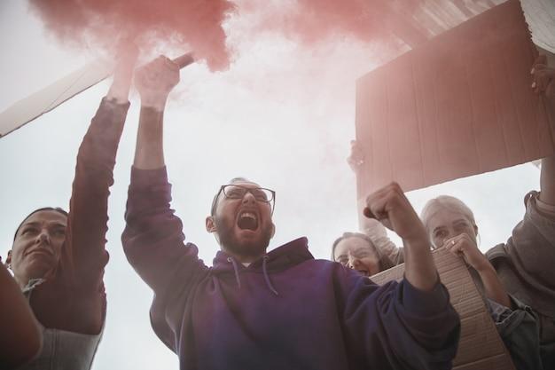 Grupo de ativistas dando slogans em uma manifestação de homens e mulheres marchando juntos em um protesto