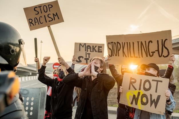 Grupo de ativistas furiosos com máscaras segurando cartazes e gritando enquanto participavam de manifestação em protesto ao racismo