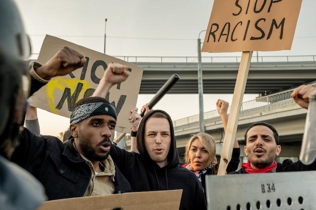 Grupo de ativistas inter-raciais descontentes levantando punhos e faixas enquanto discursam contra o racismo na praça