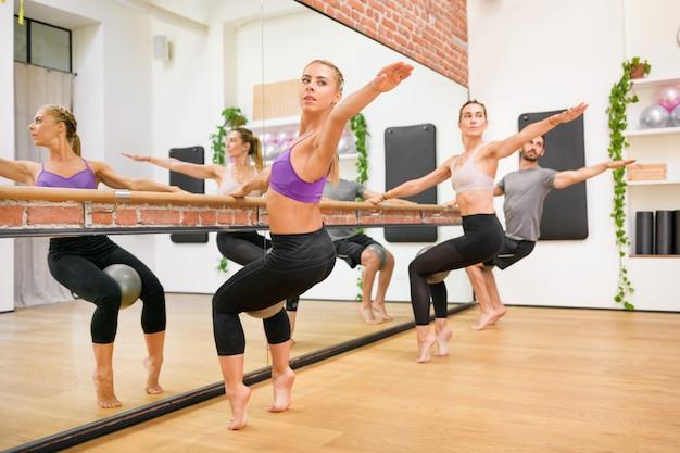 Grupo de atletas fazendo exercícios de torção espinhal