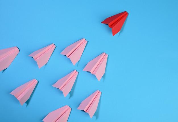 Grupo de aviões de papel rosa segue o primeiro vermelho contra um fundo azul. o conceito de unir uma equipe para atingir objetivos, um líder forte, um grupo altamente eficaz, visão superior