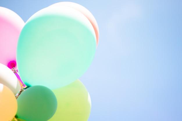Grupo de balão pastel macio com colorido na luz - céu azul.