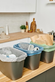 Grupo de baldes de plástico para resíduos padrão na mesa da cozinha