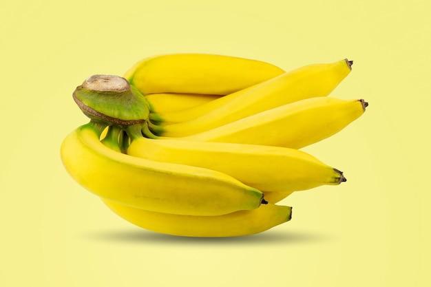 Grupo de bananas maduras descascadas amarelas no mesmo galho, isolado em um fundo de cor pastel amarelo.