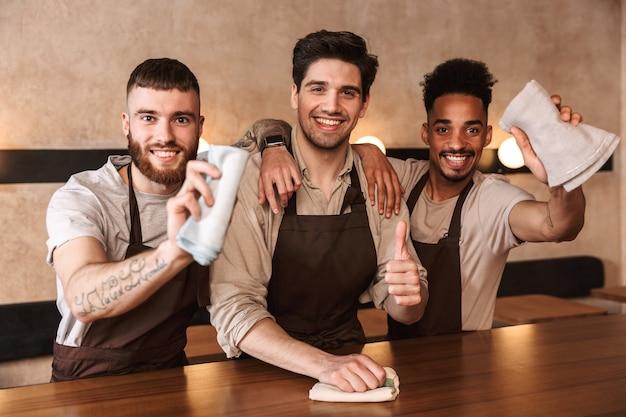 Grupo de baristas alegres usando aventais, trabalhando em um café dentro de casa, limpando as mesas