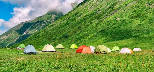 Grupo de barracas de camping coloridas em acampamento com montanhas ao fundo e céu nublado
