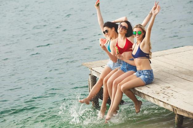 Grupo de belas mulheres alegres, descansando com melancia na praia. rindo namoradas no lado do mar se divertindo. bronzeamento de mulheres bonitas
