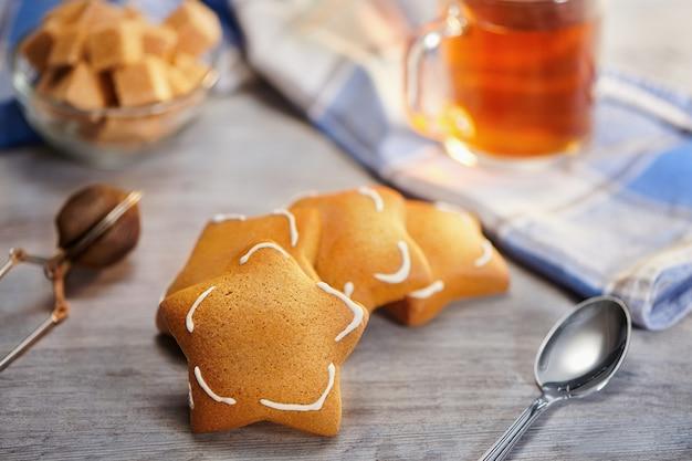 Grupo de biscoitos de gengibre em forma de estrela recém-assados na mesa de madeira. foco seletivo, conceito de hora do chá de aquecimento no inverno congelado.