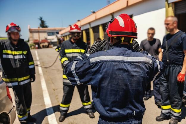 Grupo de bombeiros ao ar livre em uniformes e capacetes de proteção e se preparando para a ação.