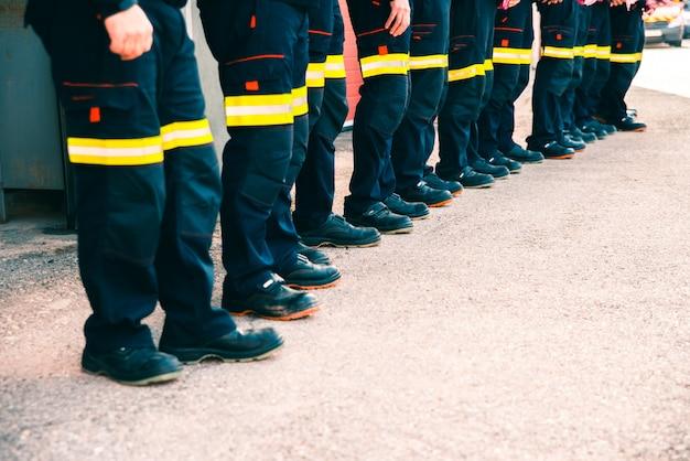 Grupo de bombeiros fazendo trabalho em equipe, vestido com seus uniformes de trabalho.