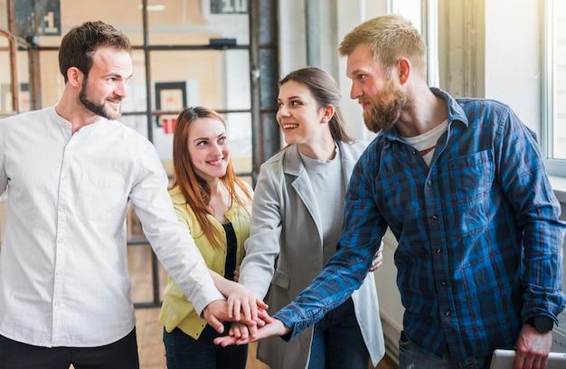 Grupo, de, businesspeople, empilhando, seu, mão, em, escritório