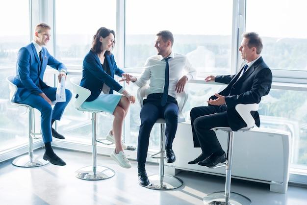 Grupo, de, businesspeople, sentando, ligado, tamborete, em, escritório