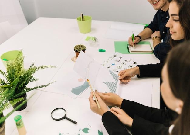 Grupo, de, businesspeople, trabalhando, ligado, gráfico, em, escritório
