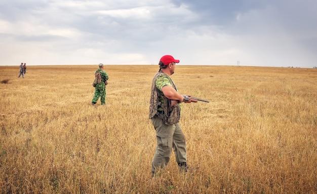 Grupo de caçadores com armas se movendo pelo campo em busca de presas