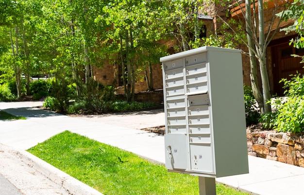 Grupo de caixas de correio de metal estão na calçada.