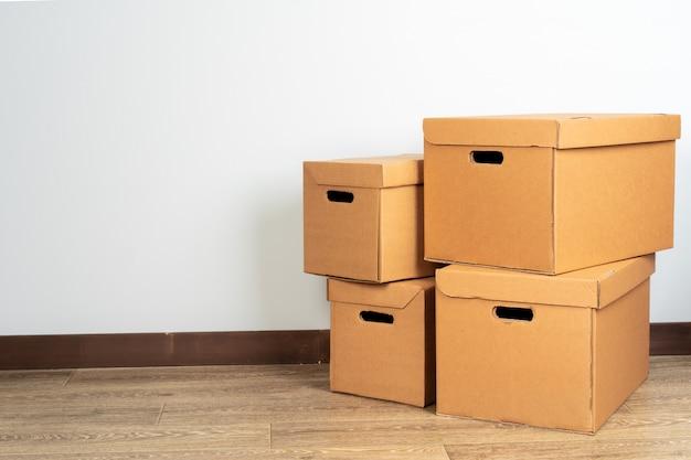 Grupo de caixas de papelão marrom no chão de madeira
