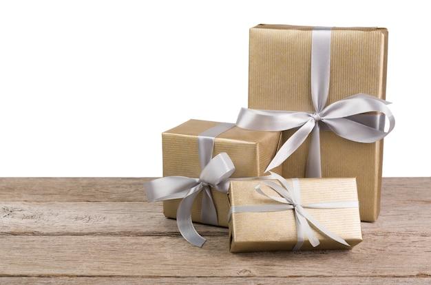 Grupo de caixas de presente embrulhadas com papel dourado e fita prateada isolada no branco