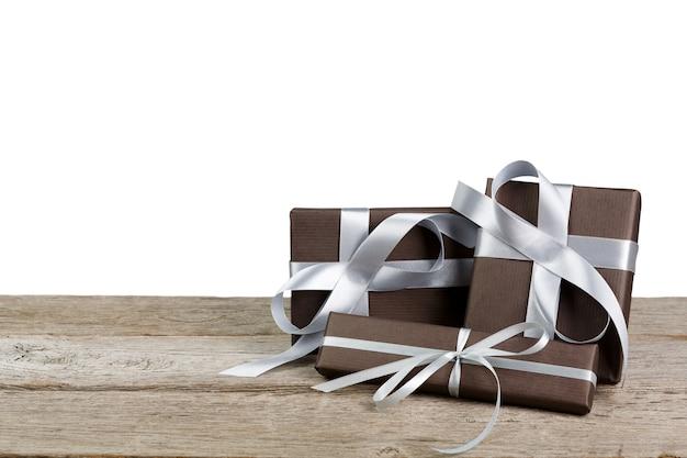 Grupo de caixas de presente embrulhadas com papel e fita de cetim prata na madeira