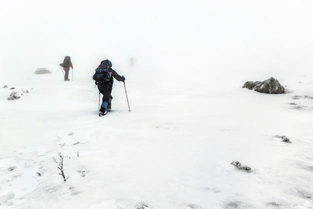 Grupo de caminhada na montanha com mochilas e bastões de trekking, fazendo uma escalada difícil durante uma tempestade de neve