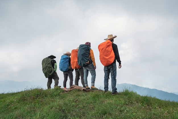Grupo de caminhadas aventuras em pé sobre uma crista. tempo limpo, céu claro
