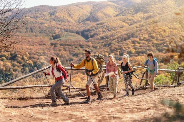 Grupo de caminhantes andando na fila e explorar a natureza. tempo de outono.
