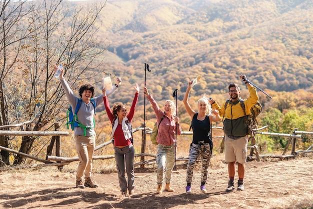 Grupo de caminhantes, com as mãos para cima e olhando para a câmera. comprimento total, outono.