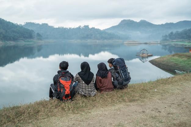 Grupo de caminhantes descansando ao lado do lago