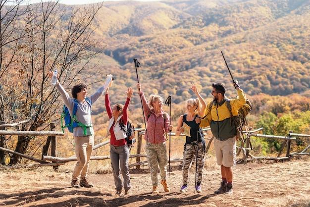 Grupo de caminhantes felizes com as mãos para cima posando na clareira. no fundo montanhas e florestas. tempo de outono.