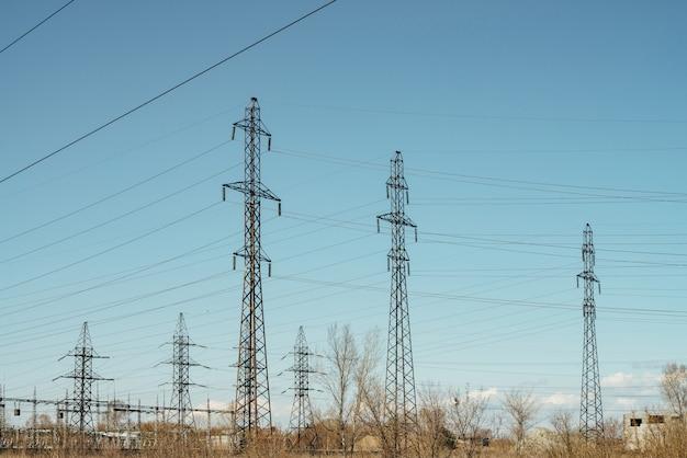 Grupo de cargos com fios de alta tensão na cena do céu azul.