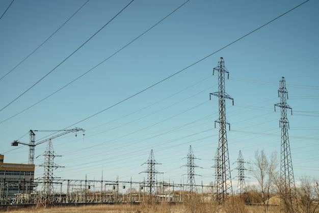 Grupo de cargos com fios de alta tensão no céu azul.