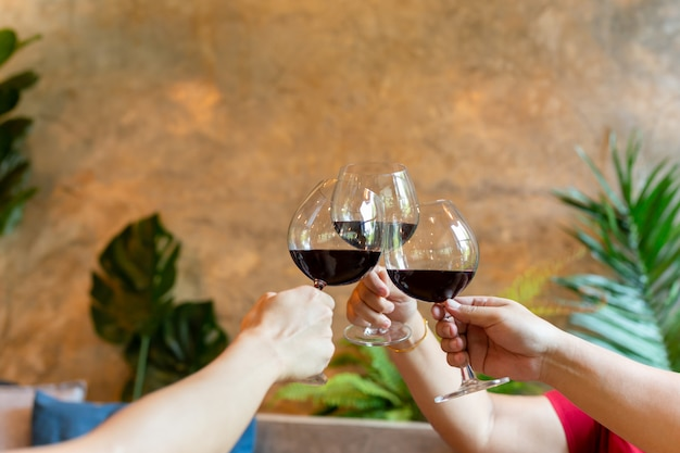 Grupo de celebração dos amigos que cheering com vinho tinto no restauran.