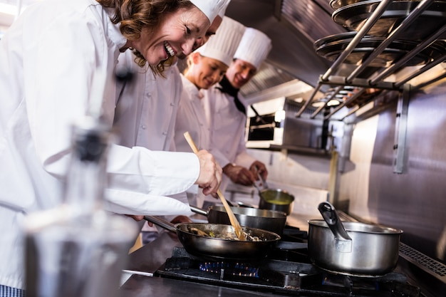 Grupo de chef preparando comida na cozinha