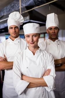 Grupo de chefs em pé com os braços cruzados na cozinha