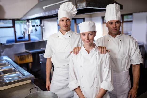 Grupo de chefs em pé na cozinha