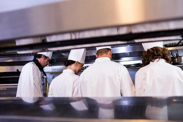 Grupo de chefs em uniforme branco ocupado para preparar comida