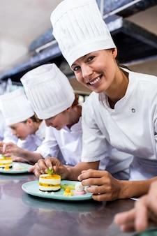 Grupo de chefs enfeitar deliciosas sobremesas em um prato