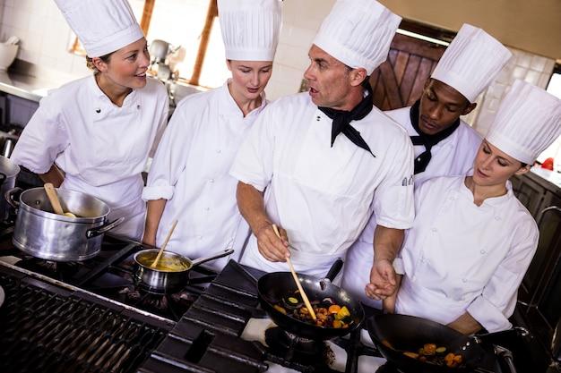 Grupo de chefs preparando comida na cozinha