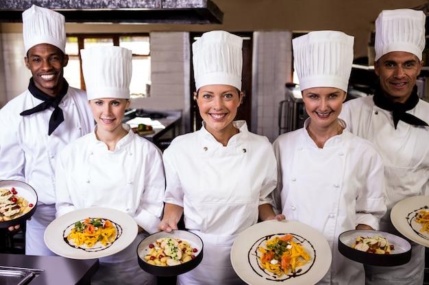 Grupo de chefs segurando o prato de macarrão preparado na cozinha