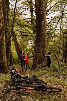 Grupo de ciclistas descansando ao ar livre, deixando suas mountain bikes no chão
