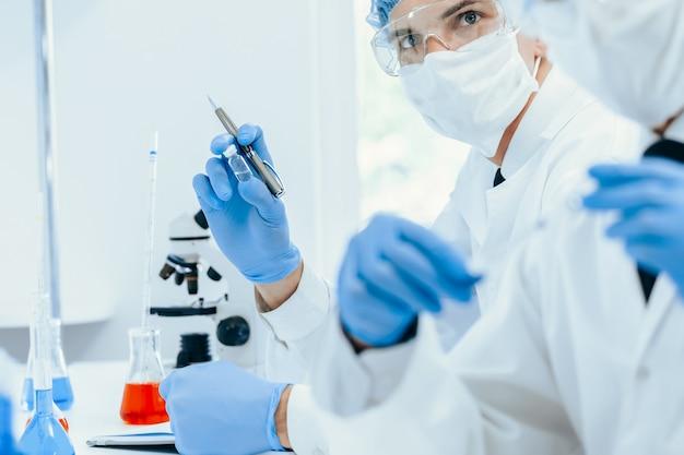 Grupo de cientistas em roupas de proteção trabalhando no laboratório