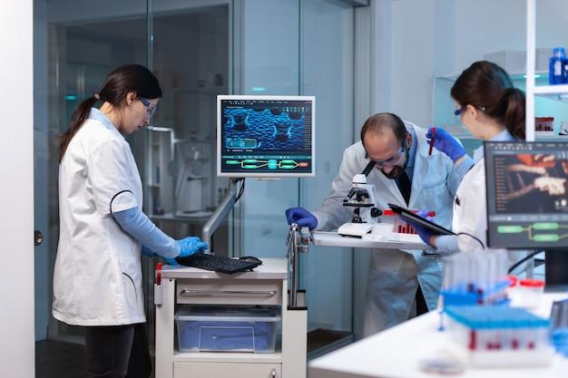 Grupo de cientistas fazendo pesquisas e experimentos no laboratório médico contra doenças com equipamentos especiais