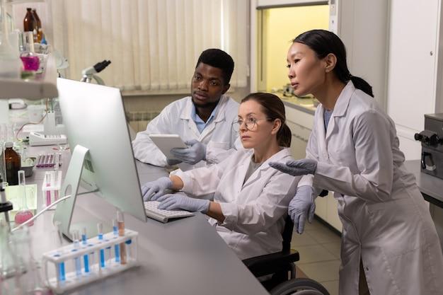 Grupo de cientistas sentado à mesa olhando para o monitor do computador e trabalhando no computador em equipe no laboratório