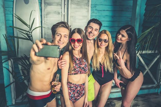 Grupo de cinco amigos comemorando em sua casa de praia no verão
